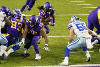 Minnesota Vikings running back Dalvin Cook (33) scores on a 1-yard touchdown run ahead of Dallas Cowboys linebacker Leighton Vander Esch (55) during the first half of an NFL football game, Sunday, Nov. 22, 2020, in Minneapolis. (AP Photo/Jim Mone)