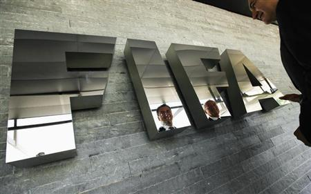 Michael J. Garcia, Chairman of the investigatory chamber of the FIFA Ethics Committee (L) and Hans-Joachim Eckert, Chairman of the adjudicatory chamber of the FIFA Ethics Committee are reflected on a logo as they pose for photographers after a news conference at the Home of FIFA in Zurich July 27, 2012. REUTERS/Michael Buholzer