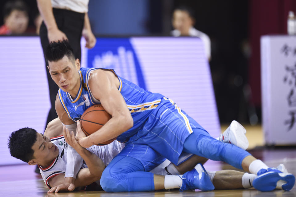 Jeremy Lin in a blue uniform holds a ball on the ground over an opponent.