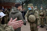 A masked President Zelensky greets an army officer in the eastern town of Zolote