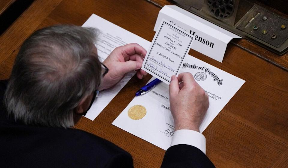 Democratic Electoral College elector Steve Henson looks at his signed vote for Joe Biden for president of the United States in Atlanta, Georgia on Monday. Photo: Reuters