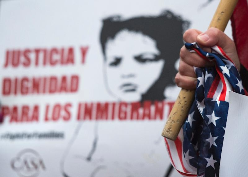 A woman clutches a US flag as other immigrants and activists protest near the White House on January 8, 2018 to demand an extension of protected status for about 200,000 immigrants from El Salvador (AFP Photo/ANDREW CABALLERO-REYNOLDS)