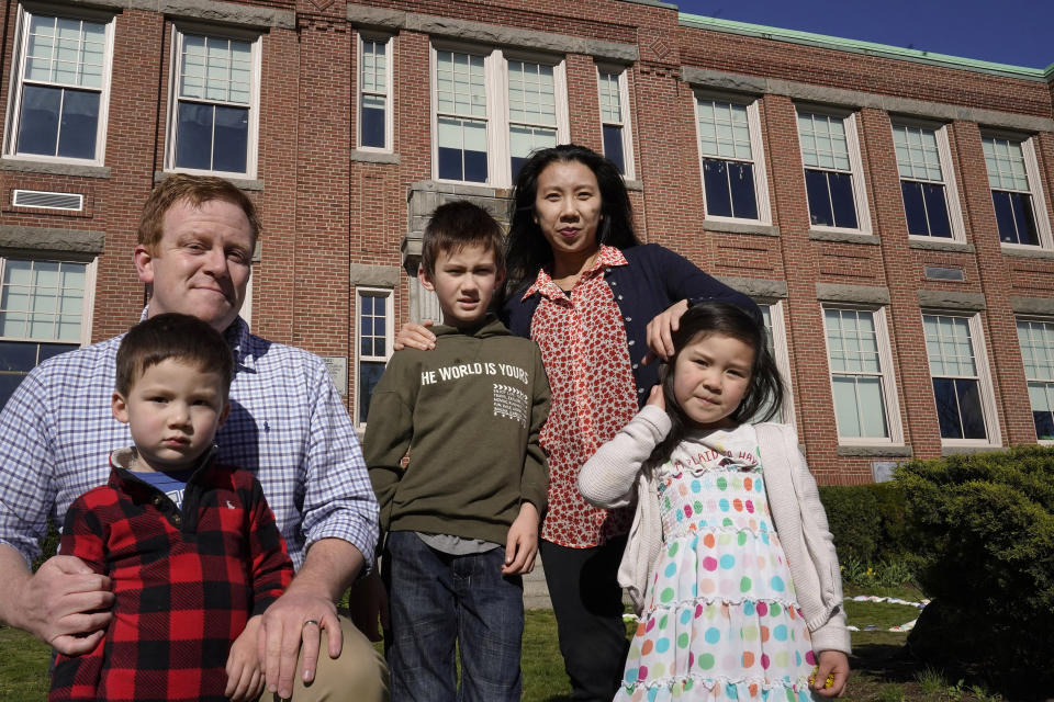 John Horrigan, top left, and his wife Kim Horrigan, top right, stand for a photograph with their children, from the left, William, 3, Conor, 8, and Sofia, 4, all of Quincy, Mass., outside Montclair Elementary School, in Quincy, Tuesday, April 13, 2021. Kim said she and her husband have struggled all year with their decision to keep their 8-year-old son in remote learning due to the coronavirus pandemic. (AP Photo/Steven Senne)