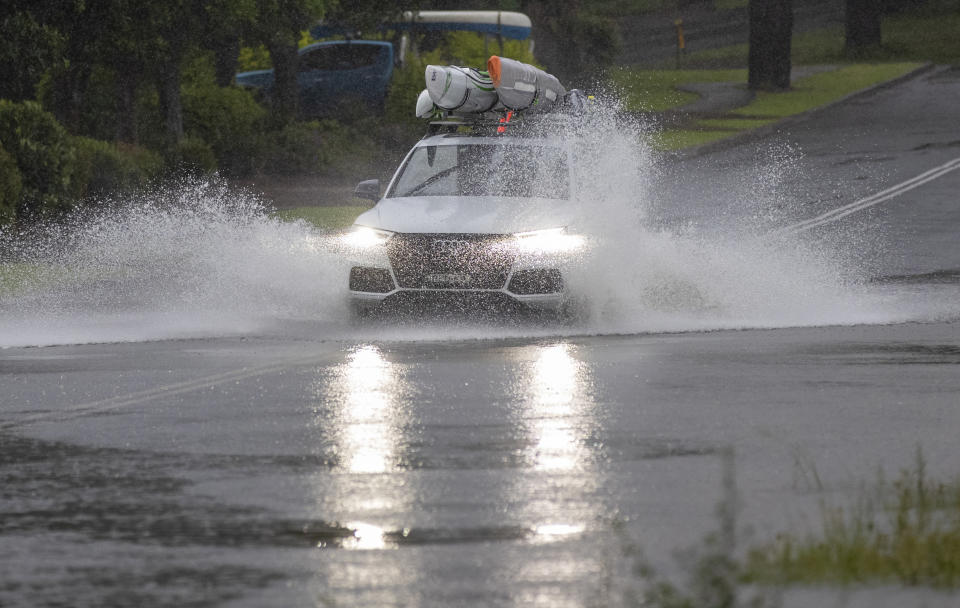 A car plows through water on a flooded road at Port Stephens, 200 kilometers (120 miles) north of Sydney, Australia, Sunday, March 21, 2021. Residents across the state of New South Wales have been warned to prepare for possible evacuations, as NSW Premier Gladys Berejiklian said the state's flood crisis would continue for several more days. (AP Photo/Mark Baker)