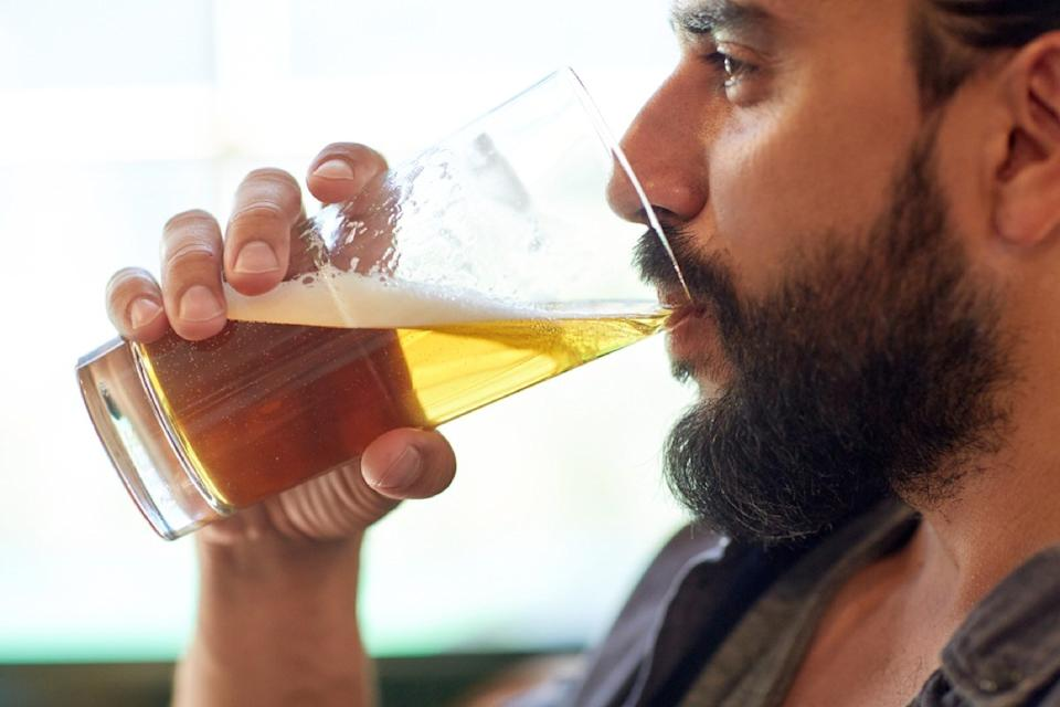 close up of bearded white man drinking a glass of beer