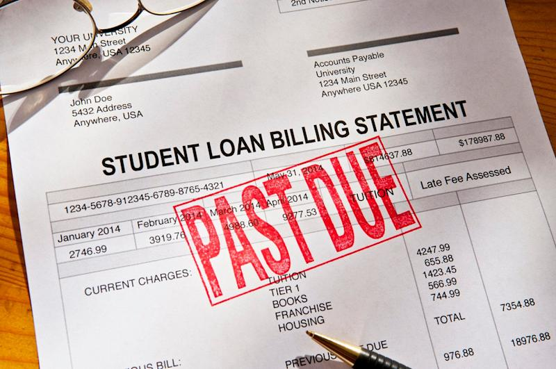 Statement for a Student Loan on a desktop. Loan is PAST DUE with a red rubber stamp. Props include reading glasses, coffee cup and pen. Horizontal photograph. PAST DUE is bright red against the white form. Shot from a high angle looking down. Dramatic lighting with some shadows.