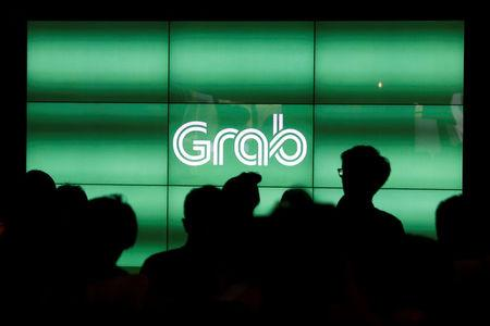 People wait for the start of Grab's fifth anniversary news conference in Singapore