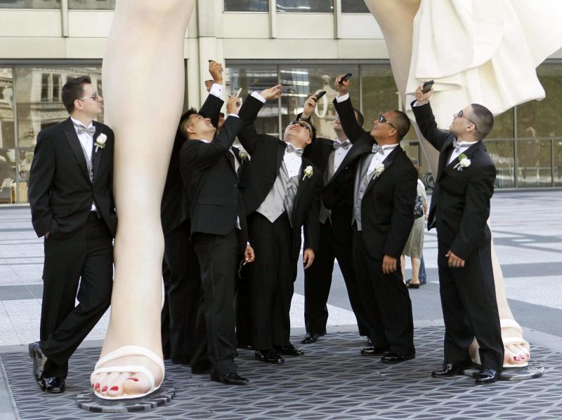 Male members of the Hugh and Anya Nguyen wedding party pose under Seward Johnson's 26-foot-tall sculpture of Marilyn Monroe, in her most famous wind-blown pose, on Michigan Ave.  Friday, July 15, 2011 in Chicago. (AP Photo/Charles Rex Arbogast)