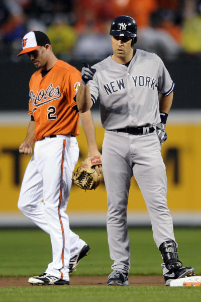 New York Yankees' Mark Teixeira (25) gestures as he stands on second after he doubled as Baltimore Orioles shortstop J.J. Hardy (2) looks down during the first inning of a baseball game, Saturday, Sept. 8, 2012, in Baltimore. (AP Photo/Nick Wass)