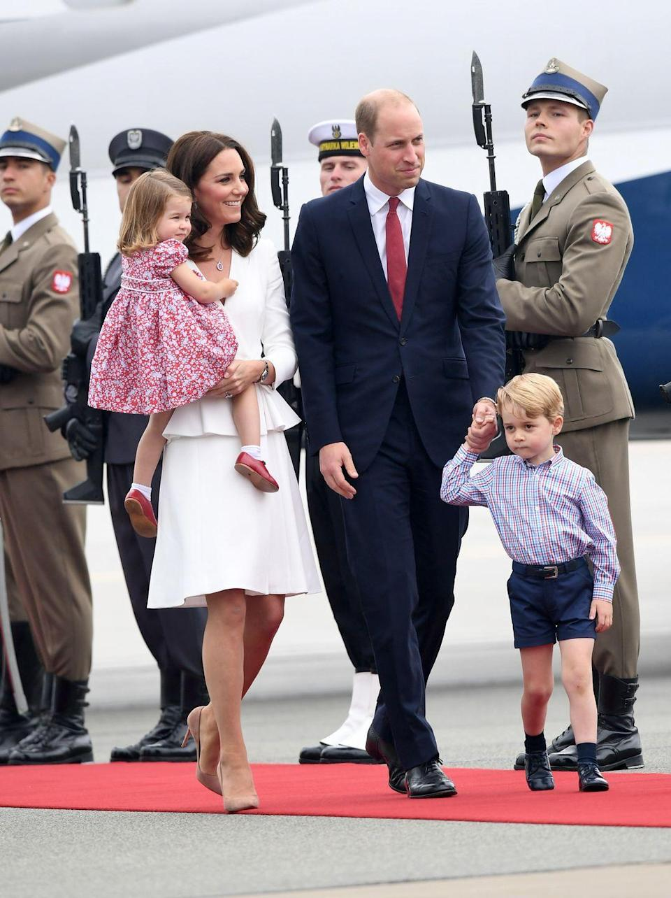 <p>The Duchess wore a white dress with a peplum as the royal family touched down in Poland to embark on the Royal Tour. She accessorized the look with nude pumps and a simple ruby necklace. </p>