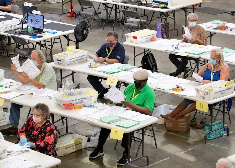 Election workers look over some of the hundreds of thousands of mail-in ballots as they are processed Oct. 16 at the Orange County Registrar of Voters in Santa Ana, California. (Photo: Mike Blake/Reuters)