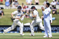 New Zealand batsmen Kane Williamson, left, and Henry Nicholls take a run during play on day two of the first cricket test between Pakistan and New Zealand at Bay Oval, Mount Maunganui, New Zealand, Sunday, Dec. 27, 2020. (Andrew Cornaga/Photosport via AP)