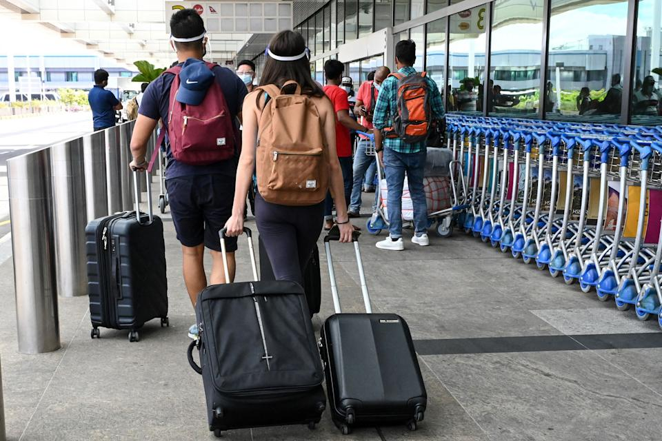 Travellers pull their luggages to enter the departure hall at Changi International Airport in Singapore.