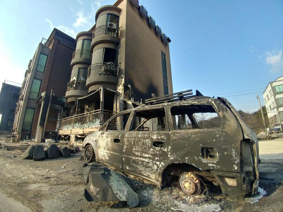 Buildings and vehicle damaged during a wildfire are seen in Goseong