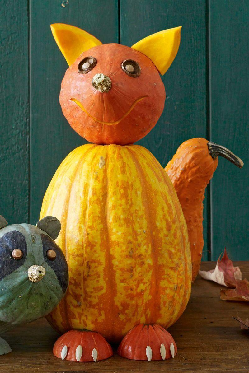 """<p>Invite this happy friend into your house or onto your front porch. He'll greet party guests and trick-or-treaters with a welcoming smile.<strong><br></strong></p><p><strong>Make the Fox Pumpkin:</strong> Stand the variegated squash straight up. Break five skewers in half and stick them into the back of the squash where the tail should sit, leaving 2"""" exposed. Press the bell-shaped orange gourd into the skewers at the back of the squash to secure as the tail. (Tip: If the skewers sink into the squash too much as you attach the gourd, simply pinch each with two fingers to hold in place while the gourd slides onto the individual skewer.) <br></p><p>Break four skewers in half and press them into the top of the squash body, leaving 2"""" exposed. Position a small pumpkin so the stem is centered where the nose should sit and push down on the skewers to secure. With the tip of the craft knife, etch out a thin smile by scraping away just the top layer of rind. To create eye sockets, etch slightly deeper holes. Remove the caps of two large acorns. Flip each cap curved-side out and press into the sockets. Remove the caps of slightly smaller acorns. Apply a dot of hot glue to each acorn and affix to the eye socket caps as pupils. Using the craft knife, cut the small pumpkin into quarters (slice in half horizontally, then in half vertically), scraping away any excess flesh with the spoon. Rinse and clean a handful of seeds. Pat dry and set aside. Cut pointy ears from two of the pumpkin quarters and press into the pumpkin head with a skewer (break, as needed), allowing the fleshy side to face forward. Turn the remaining pumpkin quarters face down and use the hot glue to affix three pumpkin seeds to each to resemble claws. Secure to the body with skewers (break, as needed).</p>"""