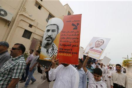 """Protesters hold banners with photos of opposition leader and head of Al Wefaq party Ali Salman saying """"We won't abandon you Bahrain"""" during a protest after Friday prayers in the village of Diraz west of Manama, Bahrain, March 11, 2016. REUTERS/Hamad I Mohammed"""