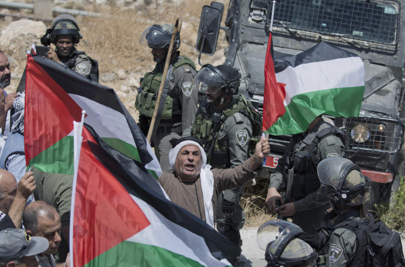 Israeli border police block the road and disperse Palestinian, Israeli and foreign activists during a rally protesting a newly established settlement near the West Bank village of Kufr Malik, East of Ramallah, Friday, Aug. 16. 2019. (AP Photo/Nasser Nasser)