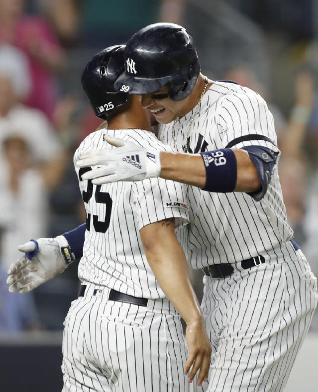 New York Yankees' Aaron Judge, right, embraces Gleyber Torres after Torres scored on Judge's two-run home run during the eighth inning of a baseball game against the Tampa Bay Rays, Tuesday, July 16, 2019, in New York. (AP Photo/Kathy Willens)