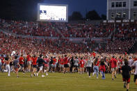 North Carolina State fans run on to the field after the Wolfpack defeated Clemson 27-21 in double overtime at an NCAA college football game in Raleigh, N.C., Saturday, Sept. 25, 2021. (AP Photo/Karl B DeBlaker)