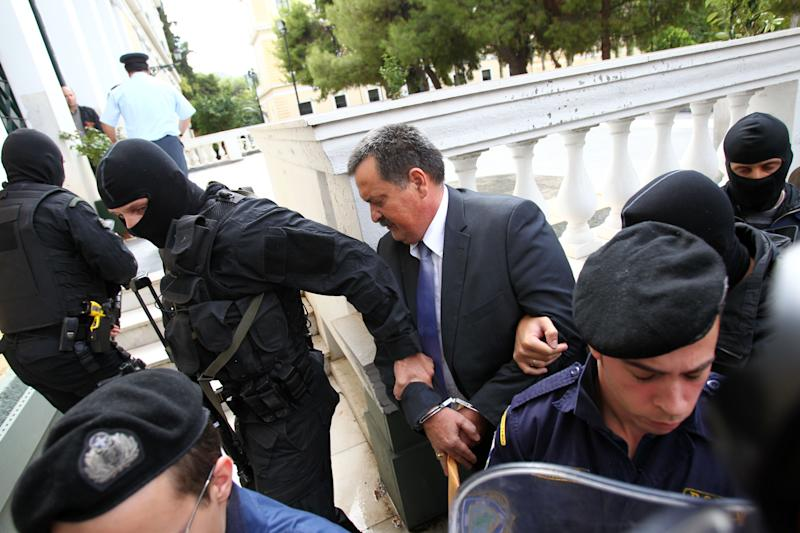Lawmaker of extremist right-wing Golden Dawn Christos Pappas, center, who the prosecution has described as the party's second in command, is escorted by anti-terror police to appear in court for his preliminary hearing in Athens, Thursday, Oct. 3, 2013. Nikos Michaloliakos, the head of Greece's extremist right-wing Golden Dawn party was jailed early Thursday, pending trial on charges of running a criminal organization in an investigation into his political party triggered by the killing of a left-wing rapper. (AP Photo/Thanassis Stavrakis)