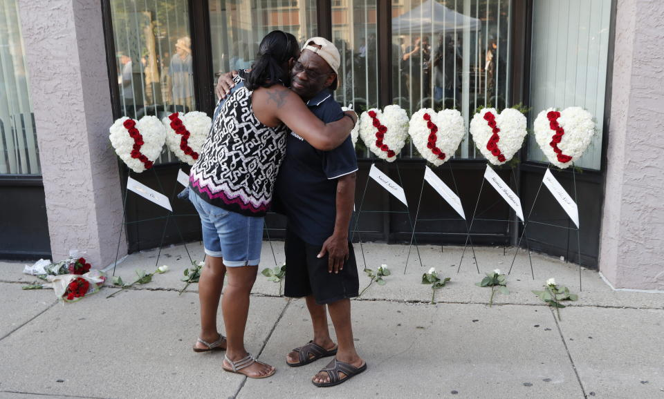 A man and a woman hug each other in front of wreaths displayed for the nine victims of a shooting in the Oregon District of Dayton, Ohio. Nine people died.