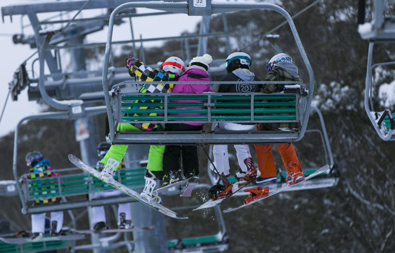 Skiers at the snow at Thredbo, NSW, sit on a chair lift.
