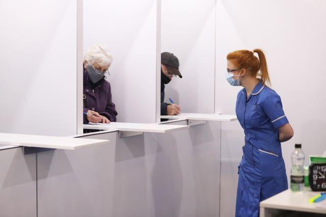Members of the public fill out paperwork before being given the Oxford/AstraZeneca coronavirus vaccine at the Elland Road vaccination centre in Leeds