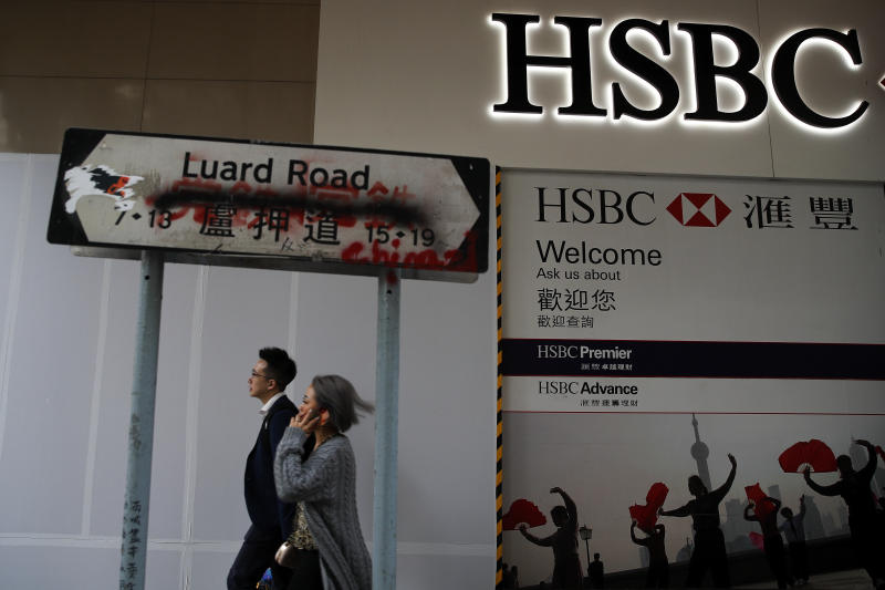 People walk by a vandalized road sign near a HSBC Bank branch covered by panels after damaged by pro-democracy protesters in Hong Kong, Saturday, Jan. 4, 2020. The months-long pro-democracy movement has extended into 2020 with further mass demonstrations. (AP Photo/Andy Wong)