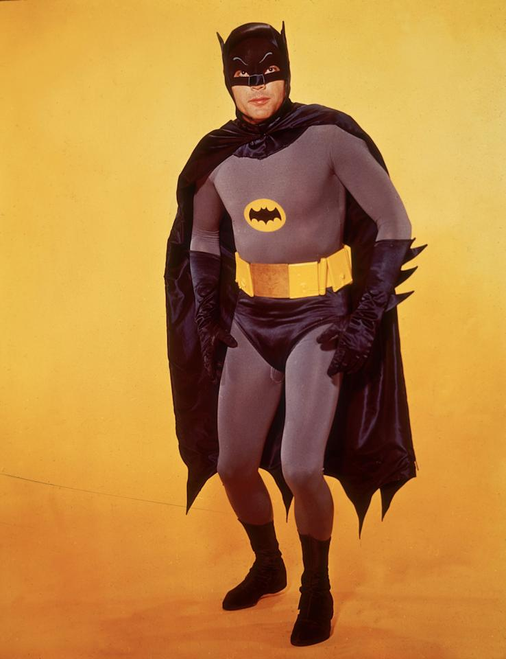 <p>Adam West poses in costume as Batman in front of a yellow backdrop in a promotional portrait for the television series, 'Batman,' circa 1966. (Photo: Hulton Archive/Getty Images) </p>
