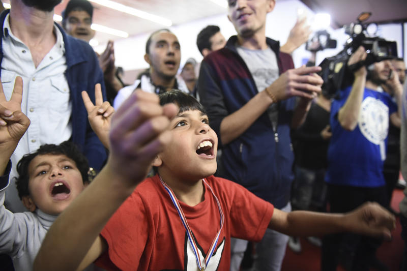 """Migrants cheer as they watch retired Spanish soccer player Carles Puyol at the Greek northern city of Thessaloniki, on Sunday, April 23, 2017. About 1000 refugees residing in northern Greece attended an event in the framework of """"Football Family Day"""" during which they watched a live broadcasting of a soccer match between Barcelona and Real Madrid on two giant screens. (AP Photo/Giannis Papanikos)"""