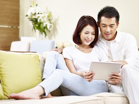 Asian man and woman reclining on a couch looking at a tablet.