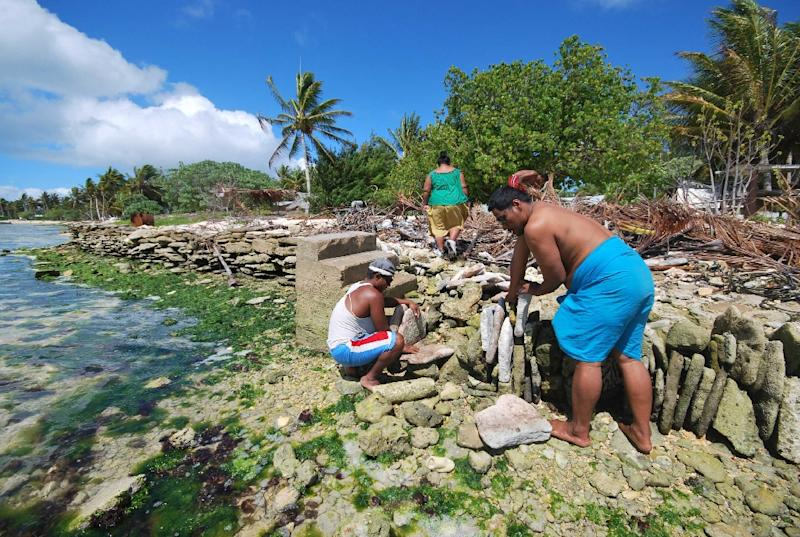 Inhabitants of Kiritimati atoll in the Pacific build a stone seawall to protect their homes as sea levels rise due to global warming (AFP Photo/)