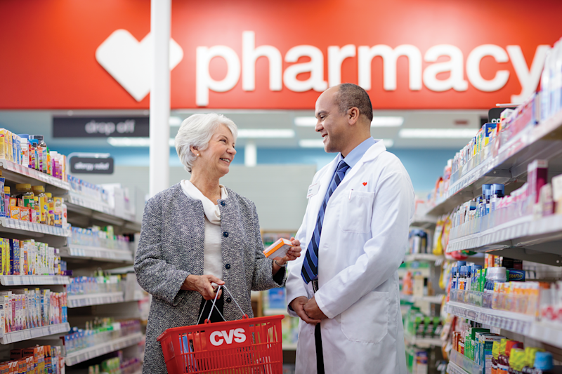 Female customer with a male pharmacist standing in the aisle of a CVS pharmacy