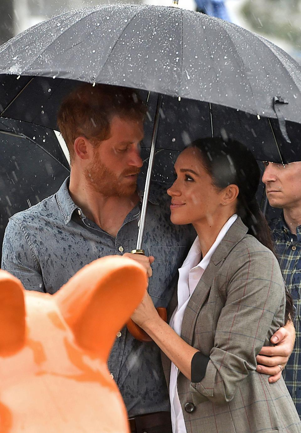 Prince Harry and Meghan Markle share an umbrella in Australia in October 2018.