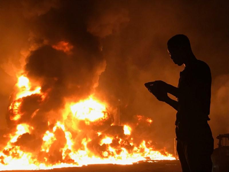 A man stands with his phone in front of flames rising from a pipeline explosion in Abula-Egba, Lagos, Nigeria