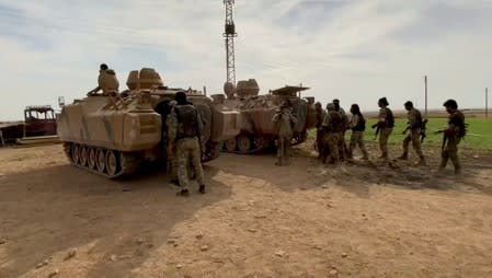 Still image from video shows Syrian rebel fighters near tanks, near Tal Abyad