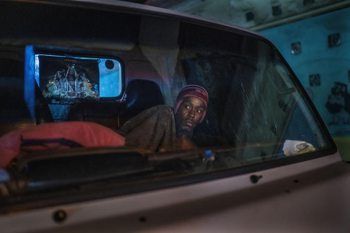A man living in his car reacts to police and army patrolling downtown Johannesburg, South Africa, Friday, March 27, 2020. Police and army started patrolling moments after South Africa went into a nationwide lockdown for three weeks in an effort to mitigate the spread to the coronavirus. The new coronavirus causes mild or moderate symptoms for most people, but for some, especially older adults and people with existing health problems, it can cause more severe illness or death.(AP Photo/Jerome Delay)