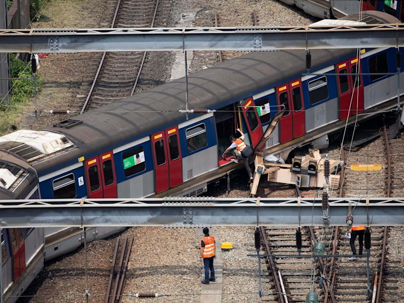 Workers investigate a derailed train in Hong Kong on 17 September 2019: EPA/JEROME FAVRE