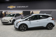 The 2022 Bolt EV, foreground, and EUV are displayed, Thursday, Feb. 11, 2021, in Milford, Mich. Whether people want them or not, automakers are rolling out multiple new electric vehicle models as the auto industry responds to stricter pollution regulations worldwide and calls to reduce emissions to fight climate change. (AP Photo/Carlos Osorio)