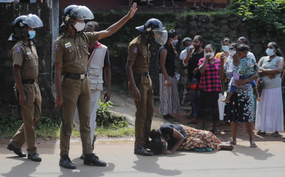 A family member of an inmate pleads lying at the feet of a policeman as she seeks information on the condition of her relative outside the Mahara prison complex following an overnight unrest in Mahara, outskirts of Colombo, Sri Lanka, Monday, Nov. 30, 2020. Sri Lankan officials say six inmates were killed and 35 others were injured when guards opened fire to control a riot at a prison on the outskirts of the capital. Two guards were critically injured. Pandemic-related unrest has been growing in Sri Lanka's overcrowded prisons. (AP Photo/Eranga Jayawardena)