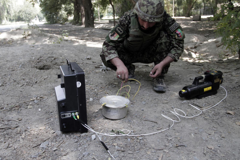 In this Tuesday, Aug. 27, 2013 photo, Afghan army soldier Ali Raza, 30, uses an x-ray machine during an IED, or improvised explosive device, defusing training exercise in Jalalabad east of Kabul, Afghanistan. After 12 years of war, roadside bombs are the No. 1 killer, claiming thousands of lives every year. As foreign troops wind down operations in preparation for their withdrawal at the end of 2014 insurgents are using an ever larger number of these explosives to assert their grip and recapture territory. (AP Photo/Rahmat Gul)