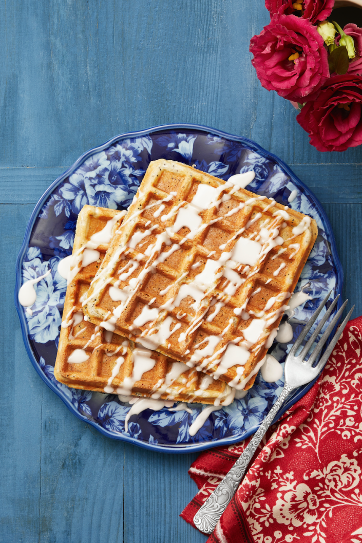 """<p>Mom will love having waffles in bed, especially if you add some special touches. These have poppy seeds and lemon zest in the batter, and they're topped with a super-simple glaze instead of syrup.</p><p><a href=""""https://www.thepioneerwoman.com/food-cooking/recipes/a33407811/lemon-poppy-seed-waffles-recipe/"""" rel=""""nofollow noopener"""" target=""""_blank"""" data-ylk=""""slk:Get the recipe."""" class=""""link rapid-noclick-resp""""><strong>Get the recipe.</strong></a></p><p><a class=""""link rapid-noclick-resp"""" href=""""https://www.amazon.com/waffle-irons/b?ie=UTF8&node=289942&tag=syn-yahoo-20&ascsubtag=%5Bartid%7C2164.g.36145857%5Bsrc%7Cyahoo-us"""" rel=""""nofollow noopener"""" target=""""_blank"""" data-ylk=""""slk:SHOP WAFFLE IRONS"""">SHOP WAFFLE IRONS</a></p>"""