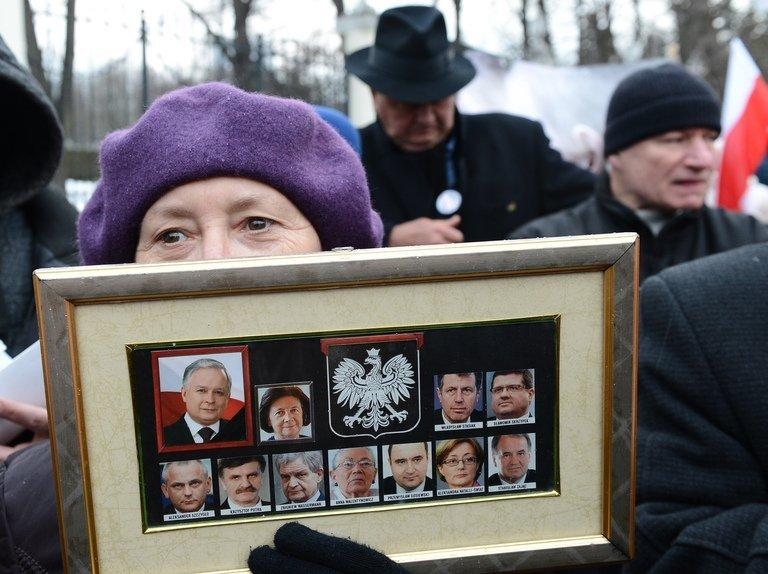 A demonstrator holds portraits of 11 of the 96 victims of the April 10, 2010 air crash in Russia of an official jet in which then Polish president Lech Kaczynski was killed, during a demonstration on April 9, 2013 in front of the Russian embassy in Warsaw. Poland's opposition leader laid flowers Wednesday in honour of Lech, who was his twin