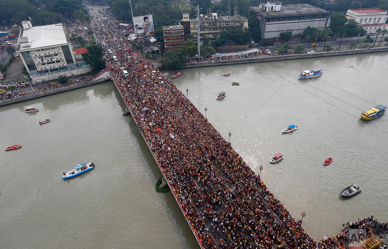 <p>Philippine Coast Guard rescue boats are on standby as Filipino Roman Catholic devotees jam the Jones Bridge during a raucous procession to celebrate the feast day of the Black Nazarene in Manila, Philippines. A massive crowd of mostly barefoot Filipino Catholics joined the annual procession of a centuries-old statue of Jesus Christ under tight security. (AP Photo/Bullit Marquez) </p>