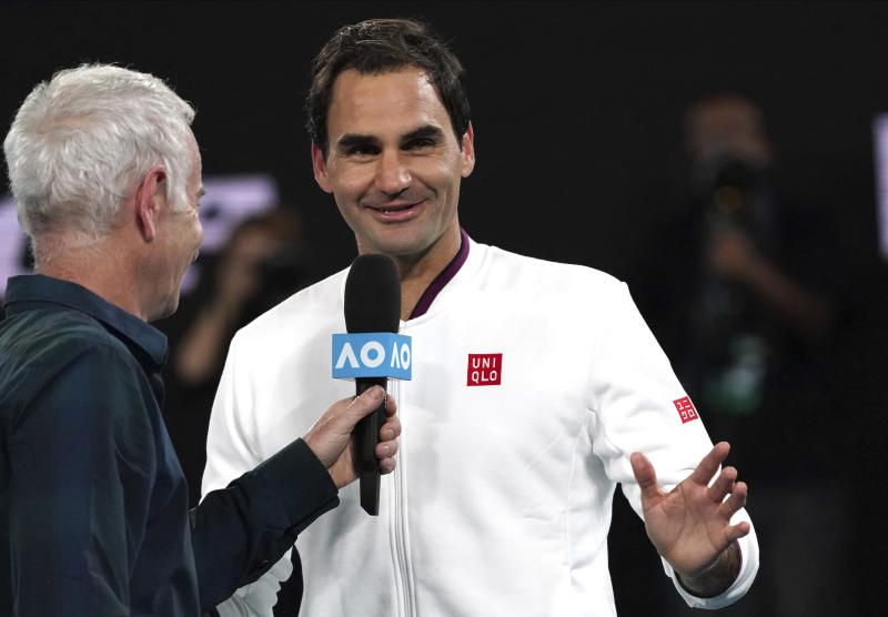 Switzerland's Roger Federer, right, reacts as he is interviewed by John McEnroe after defeating Hungary's Marton Fucsovics in their fourth round singles match at the Australian Open tennis championship in Melbourne, Australia, Sunday, Jan. 26, 2020. (AP Photo/Lee Jin-man)