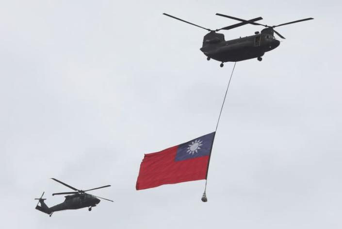 A Taiwan flag flews across the sky during National Day celebrations in Taipei