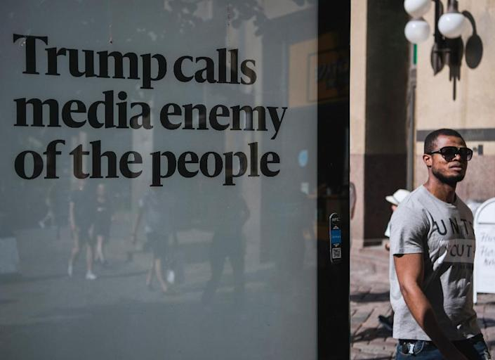 """A man walks past an advertising board reading """"Trump calls media enemy of the people"""" on the sidelines of a meeting between US President and his Russian counterpart on July 16, 2018 in Helsinki, Finland (AFP Photo/Jonathan NACKSTRAND)"""