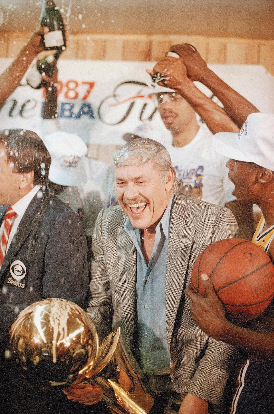 FILE - In this June 15, 1987 file photo, Los Angeles Lakers owner Jerry Buss gets doused with champagne from members of his team as he holds the NBA Championship trophy after the Lakers defeated the Boston Celtics 106-93 to win the NBA Championship four games to two in Inglewood, Calif. Buss, the Lakers' playboy owner who shepherded the NBA franchise to 10 championships, has died. He was 80. Bob Steiner, an assistant to Buss, confirmed Monday, Feb. 18, 2013 that Buss had died in Los Angeles. Further details were not available. (AP Photo/Lennox Mclendon, File)