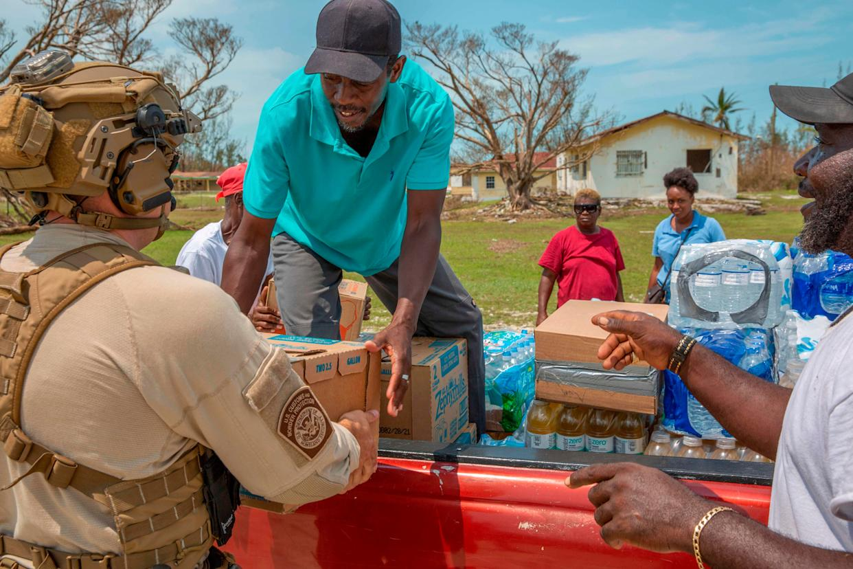 In this image courtesy of US Customs and Border Protection (USCBP), USCBP agents deliver food and water to severely damaged Fox Town on the Abaco Islands in the Bahamas, on September 6, 2019, in the aftermath of Hurricane Dorian. - The death toll from Hurricane Dorian's devastating rampage across the Bahamas rose to 43 and was likely to climb