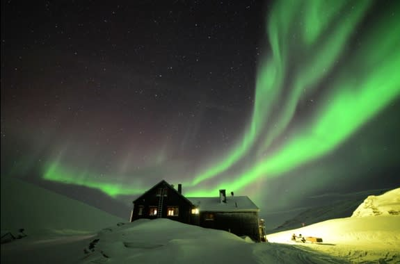 """Brilliant northern lights dance over a small hotel high in the Swedish mountains on Feb. 21, 2014 in this image from the video """"Lights Over Lapland"""" by Chad Blakley."""
